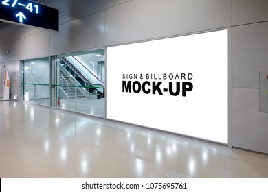 Mock up large advertisement signboard with clipping path near the sliding door entrance into airport terminal hall, empty white space for advertising or information to public transportation.