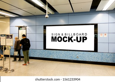Mock up large blank horizontal billboard with clipping path placed near entrance and walkway in metro station, blurred people walking, empty space for advertising or information, advertising concept
