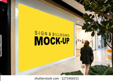 Mock up large blank yellow screen vertical billboard with clipping path at glass on front of showroom in shopping mall near hallway, perspective with empty space for advertising information