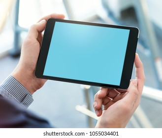 Mock up of a man holding digital tablet device in hands. Clipping path