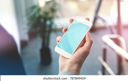 Mock up of a man holding smartphone in hand. Clipping path