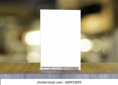 Mock up Menu frame in Bar restaurant ,Stand for booklets with white sheets of paper acrylic tent card on wooden table on