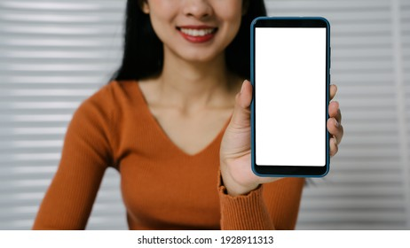 Mock up mobile blank white screen on hands of Asian woman while sitting.