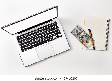 Mock up on laptop screen and money on white notebook. Book with money and Laptop flat layout.