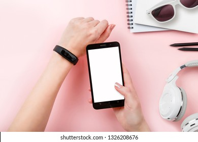 mock up phone in hands with Fitness tracker, headphones, glasses on pink background. Copy space. 'To do' list. Planning of walk route, to-do list or shopping. Smart Band Sport bracelet app