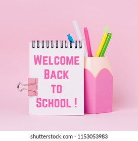 Mock up picture of notebook and pencil holder on pink background. Text 'Wellcome back to school'.