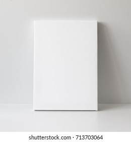 Mock up poster. Empty white canvas, gray wall and floor on background.