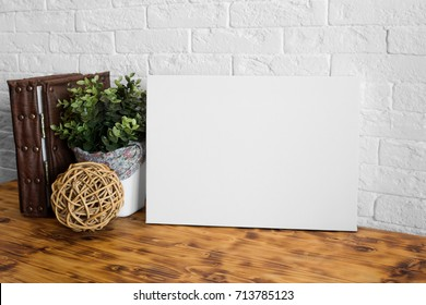 Mock up poster in the interior. Blank canvas frame. Wooden table and white brick wall on background.
