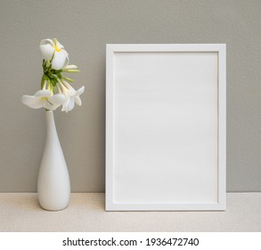 Mock up poster white frame and beautiful Plumeria or Frangipani tropical floral in modern white vase on beige table and cement wall background