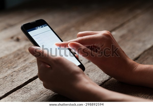 mock up of smart phone and girl holding it over a wooden table