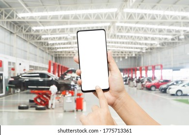 Mock up smartphone for automobile online service mobile application. Mockup blank white screen mobile phone with finger point and touch on touchsreen in  Auto repair shop.