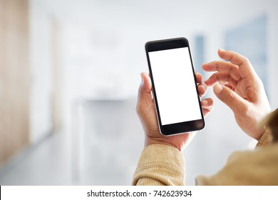 Mock up smartphone blank screen in man hands in blurred office interior background.