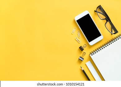 Mock up smartphone and office accessories on colorful background with copy space.view from above