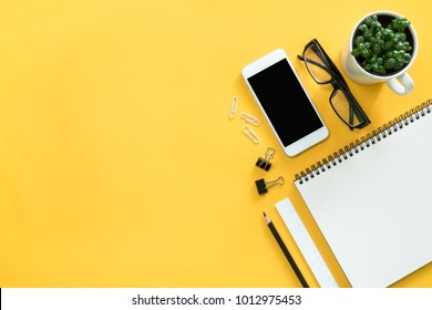 Mock up smartphone with office accessories on yellow background