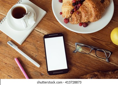 Mock up of smart-phone at a wooden table with glasses, coffee, croissants with berries