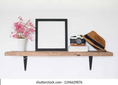 Mock up square frame photo on wooden shelf. Lifestyle traveler home decor concept