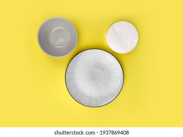 Mock up table setting on yellow background. Group of trendy ceramic utensil with plate, bowl and sauser for summer serving or restaurant menu. Minimalist style. Trendy color design