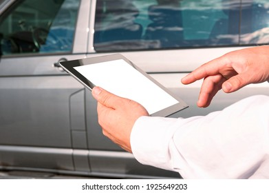 Mock up technology. Businessman in a white shirt holds a tablet with a white screen on the background of a minibus