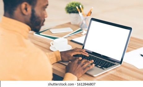 Mock Up Template. Rear view of black man working on laptop with blank screen, typing on keyboard, copyspace