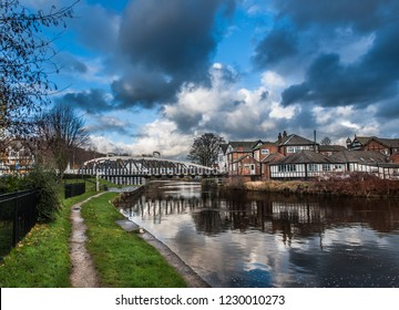 Mock tudor buildings along the river Weaver with the old swing bridge in Northwich town, Cheshire, Uk.