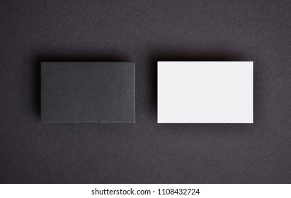 Mock up of two horizontal black and white business cards at black textured paper background. Mock-up template for branding identity.