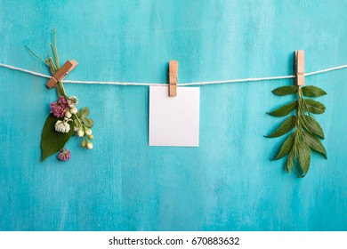 Mock up. A blank sheet of paper and a floral composition on blue wooden background.