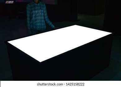 Mock up, copyspace, template, education, future and technology concept - woman looking at white blank interactive touchscreen display table kiosk in dark room of modern technology museum