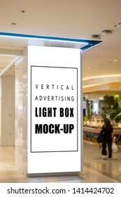 Mock up vertical blank light box with clipping path on big pole at walkway in shopping mall  and blurred people in background, empty space for advertising or information, advertising concept