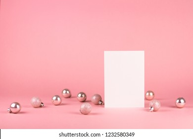 Mock up with vertical invitation card on trendy pastel light pink background with christmas ornaments. Greeting card and silver Christmas baubles. Place for text