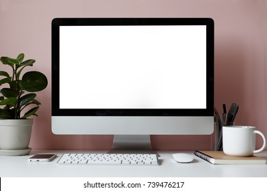 Mock up of white desktop with electronic devices, stationary items, cup of tea, copybook and decorative green plant over pinkish wall. Minimalistic modern workplace of student or freelancer