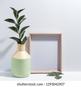 Mock up white frame and branch with green leaves in ligth-green vase on book shelf or desk. Minimalistic concept.