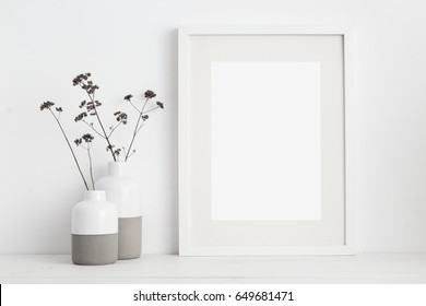 Mock up white frame and dry twigs in vase on book shelf or desk. White colors.