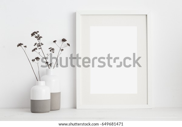 Смазайте белую рамку и сухие веточки в вазе на книжной полке или столе. Белые цвета.