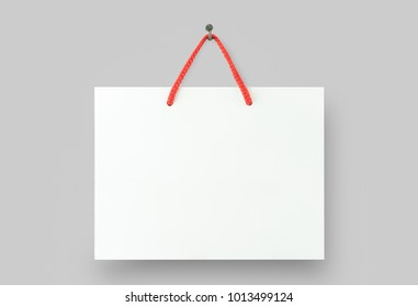 Mock up of white paper bag hanging on red rope on wall background