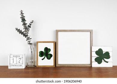 Mock up wood frame with St Patricks Day decor on a wood shelf. Shabby chic wood signs, calendar and green branches. Square frame against a white wall. Copy space.