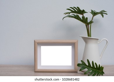Mock up wooden frame with green tropical leaves in vase on book shelft or wooden office desk with wall background with copy space
