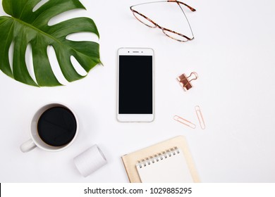 Mock up workspace with smartphone, tropical palm leaf,  glasses, notebook and coffee cup on white background. Flat lay, top view. stylish female concept.