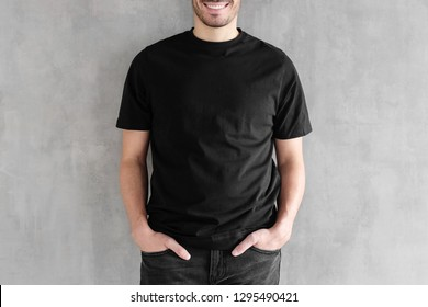 Mock up of young man body in empty black t-shirt isolated on textured gray wall background. No face photo