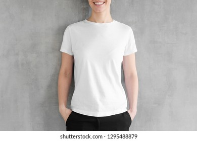Mock up of young woman body in empty white t-shirt isolated on textured gray wall background