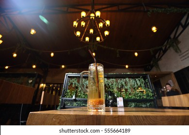 Mocktail Cocktail on Wooden table with atmosphere light restaurant ceiling, bottom view