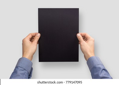 Mockup  A4 letter vertical empty blank black holds the man in his hand in shirt. Isolated on a gray background
