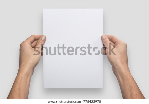 Mockup A4 letter vertical empty blank white holds the man in his hand. Isolated on a gray background