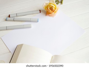 Mockup for A4 paper with single rose, book and drawing material