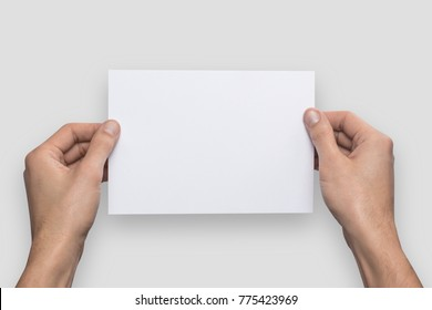 Mockup A5 letter horizontally empty blank white holds the man in his hand. Isolated on a gray background