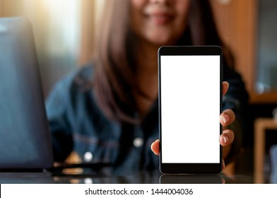 Mockup asian smiling woman hand holding and showing black mobile smart phone with blank white screen, work on computer on the desk at workplace.Business technology concept. Front view.Clipping path.