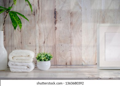 Handtücher, leeres Holzplakat und Hauspflanze auf Holztisch mit Kopienraum.
