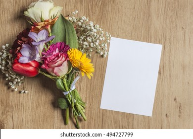 Mockup With A Beautiful Bouquet Of Spring Flowers And A Vertical Card On Wooden Surface