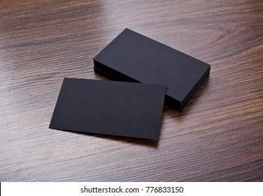 Mockup of black business cards at wooden background. Template for branding identity