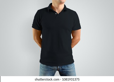 Mockup  black polo shirt on a strong guy with his hands behind his back. Isolated on a gray background. Template can be used for your design.