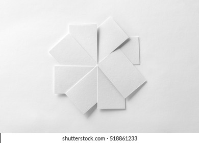 Mockup of blank business cards fan stack at white textured paper background.
